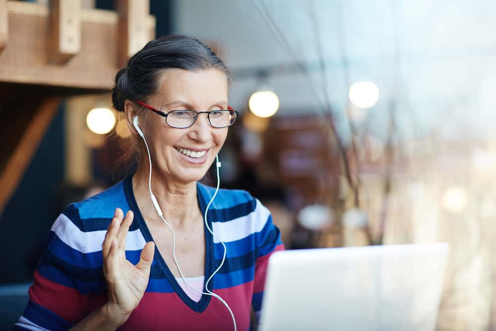 woman with headphones participating in virtual workshop on laptop